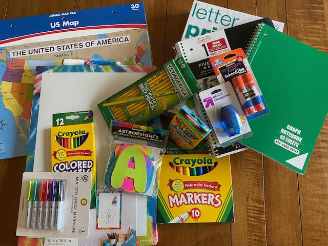Photo of school supply prizes in giveaway including Crayola markets and colored pencils, #2 pencils, pencil sharpener, glue sticks, spiral bound notebooks, US maps, and printer paper among other things.