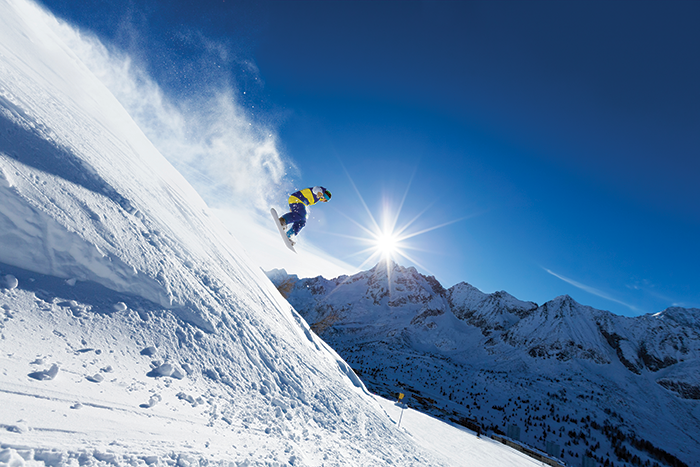 Snowboarder flying down a sunny mountain slope.