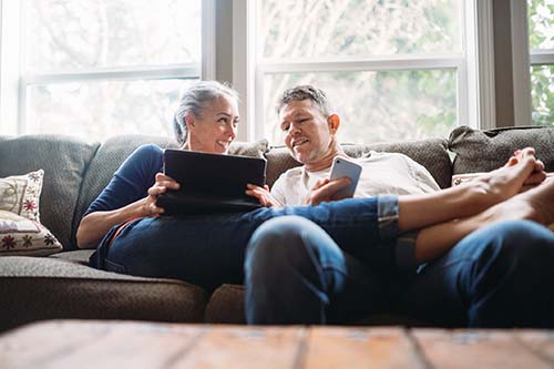 older couple sit on couch looking at tablet and smart phone