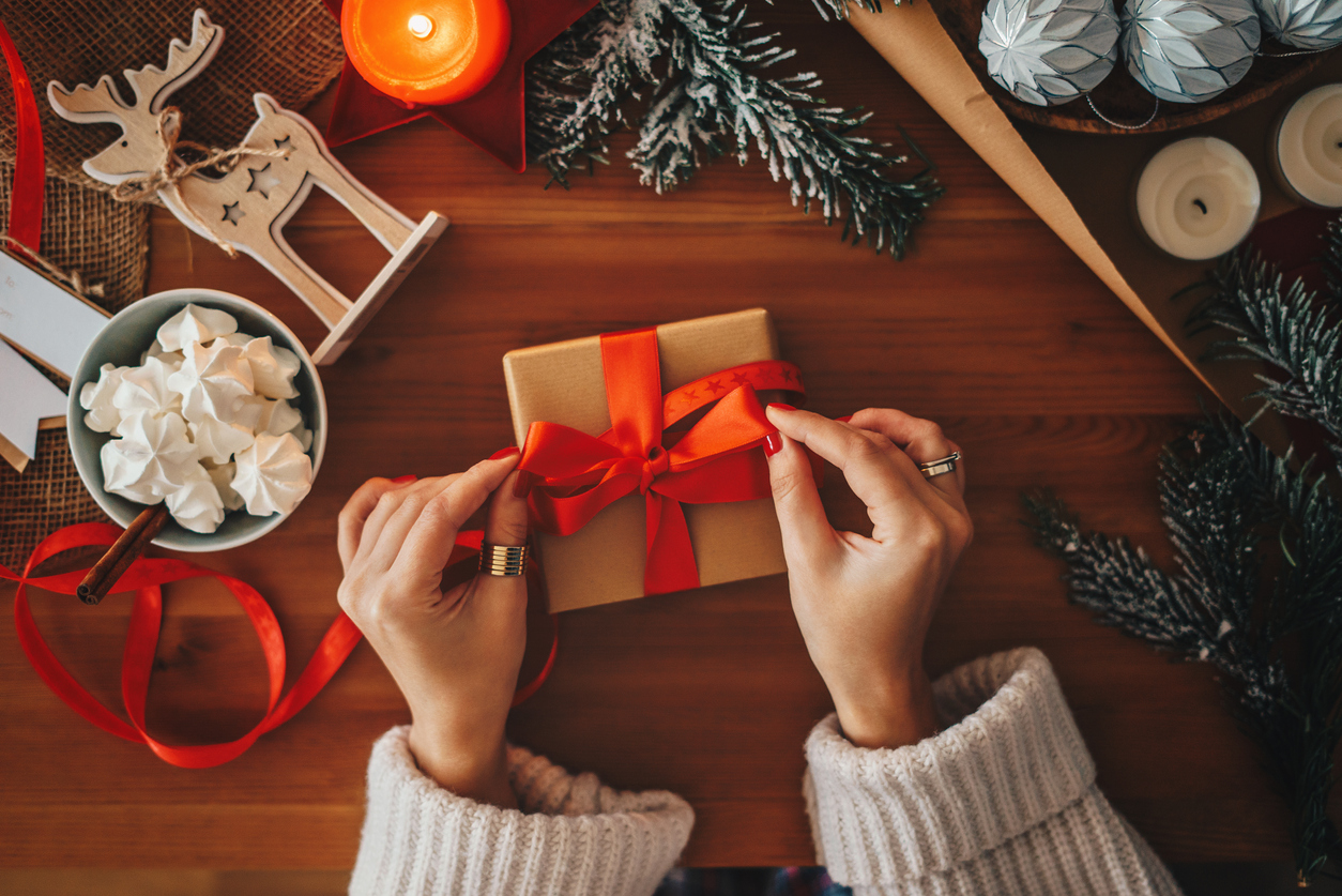 woman's hands tying a red bow around a gift, holiday items are scatter around the work surface